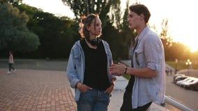 聊天与女朋友的时髦的年轻人在公园在晴朗的夏日 在谈话的爱的夫妇户外 佩带 股票视频