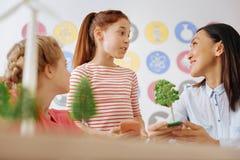 聊天与她的关于生态的老师的逗人喜爱的女小学生 免版税库存照片