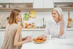 聊天与她的成熟妈妈的愉快的妇女 免版税库存图片