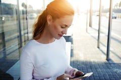 聊天与她的朋友的年轻美丽的妇女通过手机,当坐一个公共汽车站在城市时, 库存图片