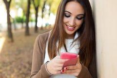 聊天与手机的美丽的女孩在秋天 库存图片