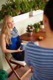 聊天与朋友的白肤金发的妇女 免版税库存图片