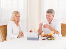 聊天与片剂的成熟夫妇笑和录影,他们吃healty早餐 免版税库存照片
