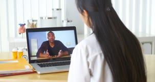 聊天与非洲患者的亚洲医生录影 免版税库存照片