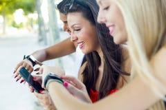 聊天与他们的智能手机的三个女孩在公园 免版税库存照片