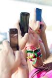聊天与他们的智能手机的三个女孩 免版税库存图片