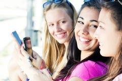 聊天与他们的智能手机的三个女孩 免版税库存照片