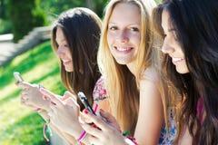 聊天与他们的智能手机的三个女孩 免版税图库摄影