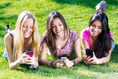 聊天与他们的智能手机的三个女孩 库存图片