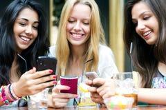 聊天与他们的智能手机的三个女孩 库存照片