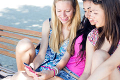 聊天与他们的智能手机的三个女孩 图库摄影