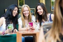 聊天与他们的智能手机的四个女孩 图库摄影