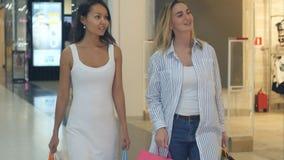 聊天两位友好的女性,当走在购物中心时 图库摄影