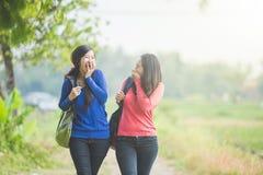 聊天两名年轻亚裔的学生,当一起时走 免版税库存图片