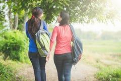 聊天两名年轻亚裔的学生,当一起走,后面v时 免版税库存图片