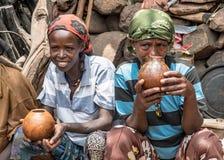 聊天和喝在他们的村庄的未认出的埃赛俄比亚的妇女 库存照片