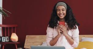 聊天和在智能手机的愉快的非裔美国人的女孩正文消息在家坐床 年轻女人接受 影视素材