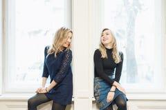 聊天和笑由窗口的两名妇女 库存图片