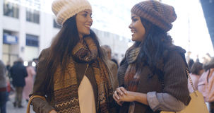 聊天在一条街道的两名妇女在冬天 免版税库存照片
