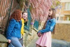 聊天在一条巴黎人街道上的美丽的女孩 免版税库存照片