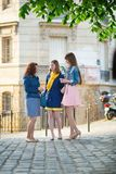 聊天在一条巴黎人街道上的美丽的女孩 免版税库存图片