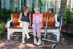 聊天在公园长椅的两个年长朋友 免版税库存照片