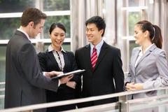 聊天在办公室之外的四个企业同事 免版税库存图片