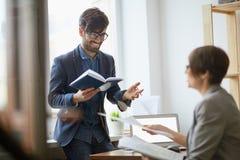 聊天在办公室的企业同事 免版税图库摄影