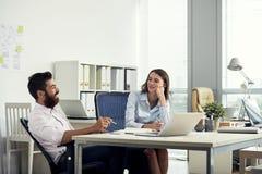 聊天在办公室的微笑的轻松的同事 免版税图库摄影