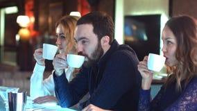 聊天在咖啡的愉快的商人在酒吧的断裂期间 库存照片