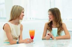 聊天在咖啡馆的二名美丽的妇女 免版税库存照片