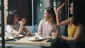 聊天在咖啡馆的快乐的学生妇女然后笑和做高五 影视素材