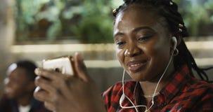 聊天在她的手机的年轻黑人妇女 图库摄影