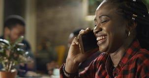 聊天在她的手机的年轻黑人妇女 库存照片