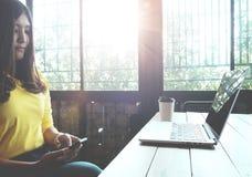 聊天在她的手机的愉快的亚裔妇女,当放松在咖啡馆在业余时间时, 图库摄影