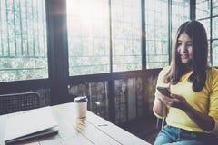 聊天在她的手机的愉快的亚裔妇女,当放松在咖啡馆在业余时间时, 免版税库存图片