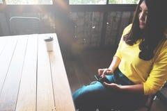聊天在她的手机的愉快的亚裔妇女,当放松在咖啡馆在业余时间时, 免版税库存照片