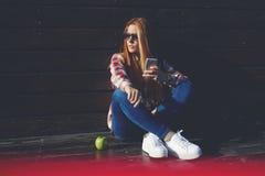 聊天在她的手机的画象时髦质朴的妇女的在休闲时间在夏日 库存照片