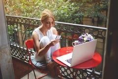 聊天在她的手机的画象年轻美丽的白肤金发的妇女的,当休息在便携式计算机上时的工作以后 免版税库存图片
