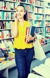 聊天在手机和采取的微笑的妇女书 免版税图库摄影