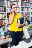 聊天在手机和采取的微笑的妇女书 免版税库存图片