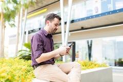 聊天在手机的人,当坐在商城之外时 库存图片