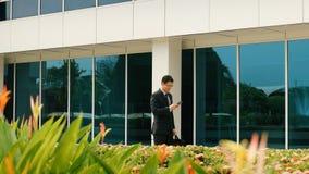 聊天在手机的商人走到办公室 库存图片