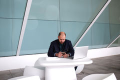 聊天在手机的男性开发商在便携式计算机上的工作以后,当坐在现代办公室内部时, 图库摄影