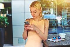 聊天在手机的迷人的行家女孩站立在咖啡店 库存照片