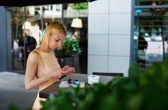 聊天在手机的迷人的行家女孩站立在咖啡店 免版税库存照片
