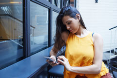聊天在手机的年轻美丽的妇女,当坐在咖啡店内部在业余时间时, 图库摄影
