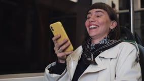 聊天在智能手机的年轻行家妇女坐在公共交通工具,steadicam射击了 年轻女人收到喜讯 股票录像