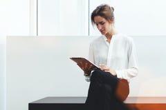 聊天在有客户的数字式片剂的年轻确信的妇女企业家,当坐在办公室内部时的长凳, 免版税库存图片