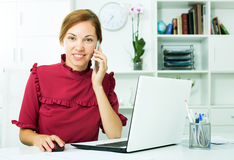 聊天在电话和使用计算机的女商人 免版税库存照片